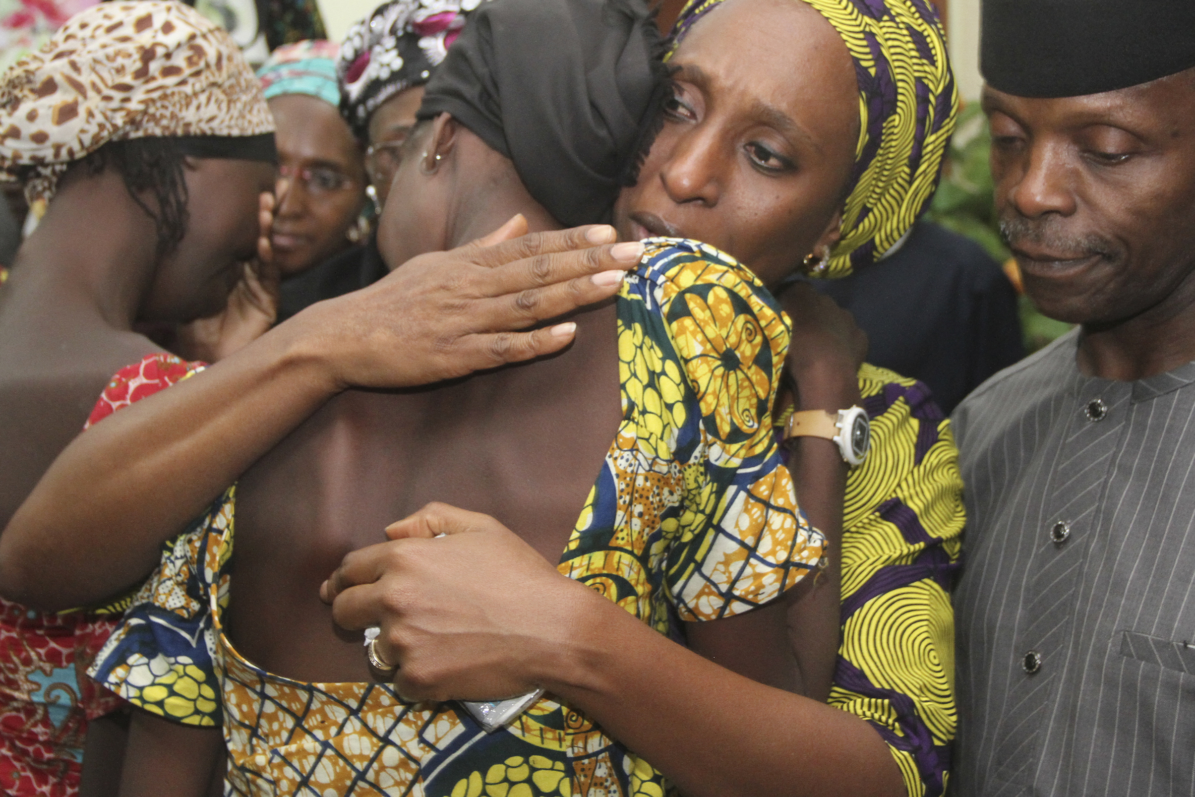 Nigerian Vice President Yemi Osinbajo (R) looks on while his wife Dolapo (C) comforts one of the 21 freed Chibok girls freed today from Boko Haram, at his office in Abuja on October 13, 2016.  Jihadist group Boko Haram has freed 21 of the more than 200 Chibok schoolgirls kidnapped more than two years ago, raising hopes for the release of the others, officials said Thursday. Local sources said their release was part of a prisoner swap with the Nigerian government, but the authorities denied doing a deal with Boko Haram. AFP PHOTO / PHILIP OJISUA