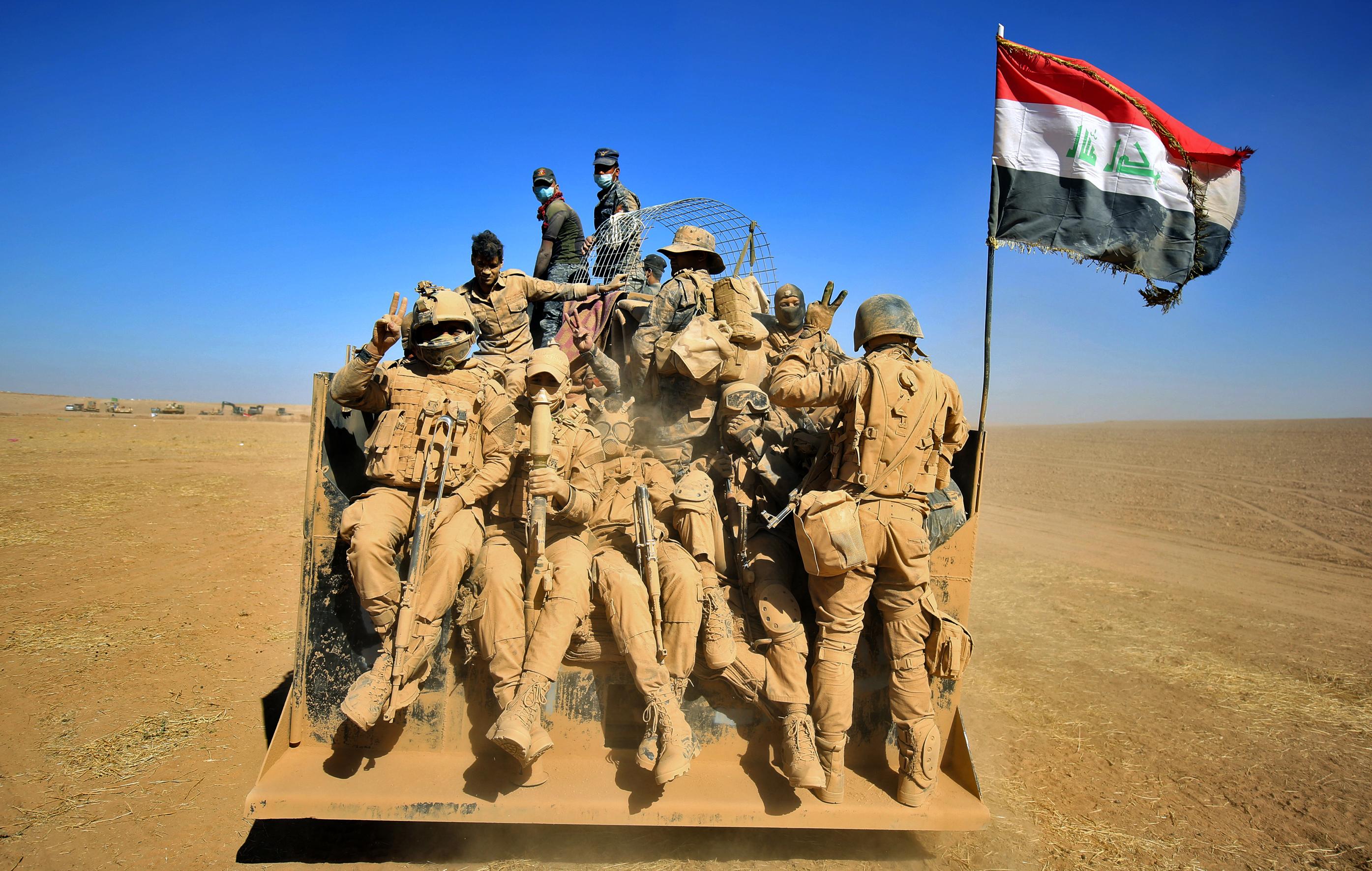 Des forces iraqiennes à l'arrière d'un véhicule de troupe, au nord-est de la base de Qayyarah, le 20 octobre 2016. / AFP PHOTO / AHMAD AL-RUBAYE