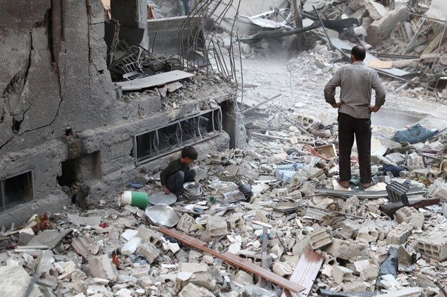 A Syrian boy collects items amidst the rubble of destroyed buildings on October 3, 2016, following reported air strikes in the rebel-held town of Douma, on the eastern outskirts of the capital Damascus. Air strikes shook a besieged rebel-held town east of the Syrian capital, sparking fears among civilians of a fate similar to battered Aleppo city. More than a dozen raids and several mortar rounds pounded Douma, said the Syrian Observatory for Human Rights monitoring group.   / AFP PHOTO / Abd Doumany